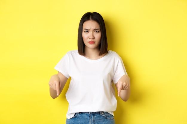 美容とファッションのコンセプト。指を下に向ける白いtシャツの美しいアジアの女性は、黄色の背景の上に立っているロゴを示しています。