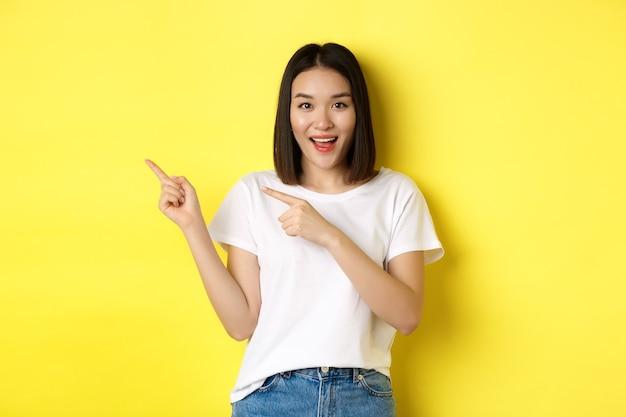 美容とファッションのコンセプト。黄色の背景の上に立って、左の指を指す白いtシャツの美しいアジアの女性。