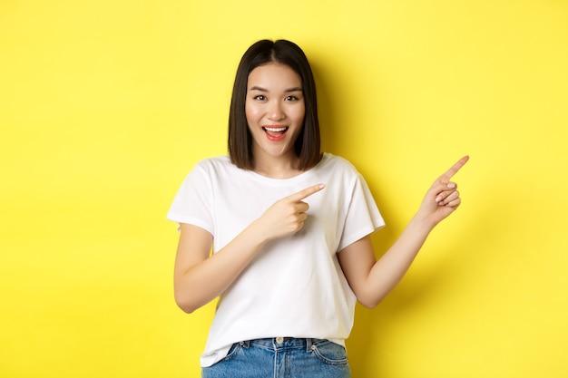 美容とファッションのコンセプト。指を右に向ける白いtシャツの美しいアジアの女性は、黄色の背景の上に立っているロゴを示しています。