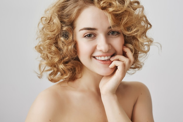 아름다움과 패션 개념. 곱슬 머리와 벌거 벗은 어깨가 웃는 평온한 아름다운 소녀