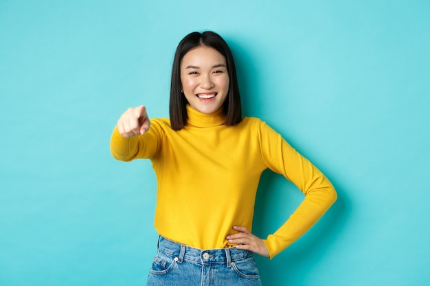 美容とファッションのコンセプト。笑って笑って、カメラに指を指して、青い背景の上に立って、あなたを選択して、陽気なアジアの女性。