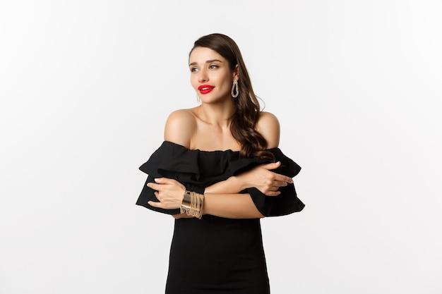 Понятие красоты и моды. элегантная и красивая женщина в черном платье с макияжем, обнимая себя и глядя чувственным взглядом, стоит на белом фоне