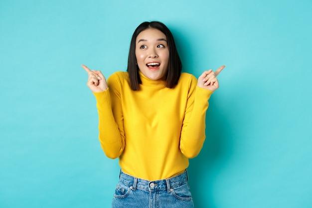 아름다움과 패션 개념. 선택을하고 손가락을 옆으로 가리키고 파란색에 서있는 두 가지 옵션 중에서 선택하는 노란색 스웨터에 흥분된 아시아 소녀.