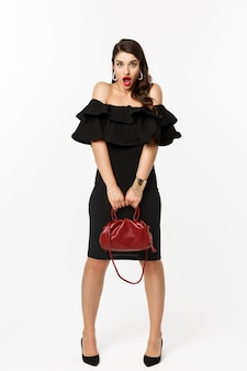 Понятие красоты и моды. полная длина, если глупая молодая женщина надувается и выглядит удивленно, держит сумочку, на каблуках и в черном платье, на белом фоне.