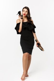 美容とファッションのコンセプト。携帯電話のようなハイヒールを使用して、白い背景に対して黒のドレスで立っている魅力的な若い女性の完全な長さ