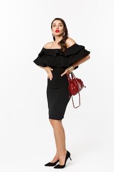 아름다움과 패션 개념. 검은 드레스, 하이힐 파티에가는 우아한 젊은 여자의 전체 길이는 카메라, 흰색 배경에서 자신감과 팬티를 찾고.