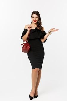 美容とファッションのコンセプト。黒のドレス、かかとと財布で買い物に行くエレガントな若い女性の完全な長さ、自信を持って、白い背景の上に立っています。