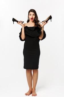 美容とファッションのコンセプト。黒いドレスを着た興奮した魅力的な女性の全長、ハイヒールを見せて興奮しているように見え、パーティーのためにドレスアップ、白い背景。