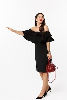 아름다움과 패션 개념. 검은 드레스와 하이힐에 매력적인 여자의 전체 길이는 택시를 멈추기 위해 손을 들고, 흰색 배경 위에 서서 타고 있어야합니다.