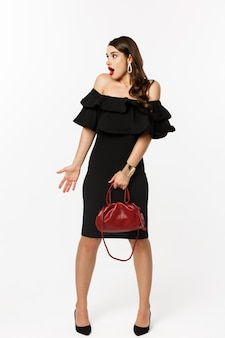 아름다움과 패션 개념. 우아한 드레스에 놀란 여자의 전체 길이, 혼란스러워 보이는 발 뒤꿈치, 지갑을 들고, 무슨 일이 일어나고 있는지, 흰색 배경을 이해할 수 없습니다.