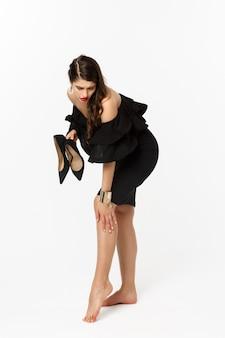 아름다움과 패션 개념입니다. 발에 통증을 느끼는 전체 길이의 여성, 하이힐을 벗고 피곤한 얼굴로 발을 문지르고 흰색 배경 위에 검은 드레스를 입고 서 있습니다.
