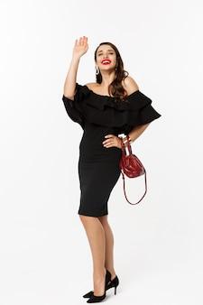 美容とファッションのコンセプト。黒のドレスとメイクで、挨拶と笑顔、挨拶に手を振って、白い背景の若い女性の完全な長さ。