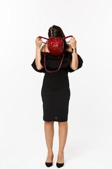 美容とファッションのコンセプト。財布の中に頭を突き刺し、何かを探して、黒いドレスとハイヒールを履いて、白い背景の上に立っている若い女性の全長