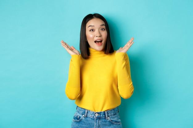 아름다움과 패션 개념. 놀랍게도 와우라고 말하는 흥분하고 놀란 일본 소녀의 이미지는 파란색에 서서 얼굴 근처에서 손을 들어 올립니다.