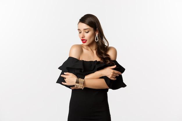 美容とファッションのコンセプト。官能的で黒いドレスと赤い唇の女性は、白い背景の上に立って、自分を抱き締めて優しく見下ろしています。