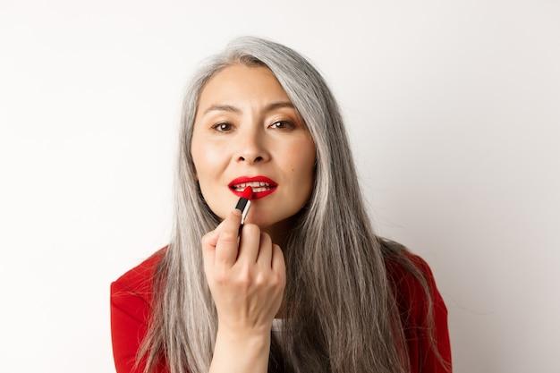 아름다움과 패션 개념. 회색 머리를 가진 세련 된 아시아 성숙한여 인, 거울을보고 흰색 배경 위에 서있는 빨간 립스틱을 적용합니다.