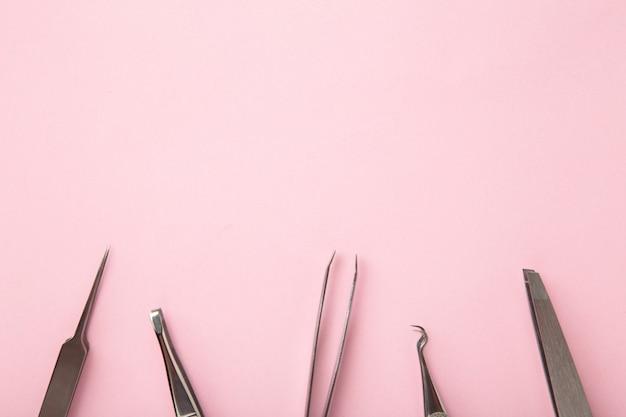 美容とファッションのコンセプト-まつげエクステの手順のためのツール。ピンクの背景にピンセット。コピースペースのモックアップ。上面図