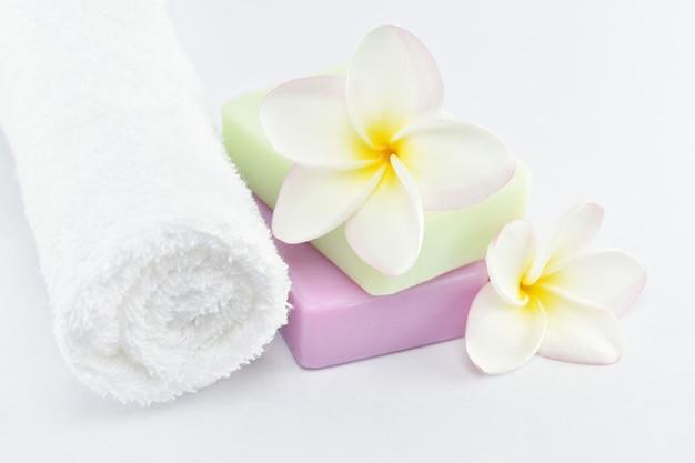 美容とファッションのコンセプトの白いタオル白い背景の上の天然石鹸とプルメリア