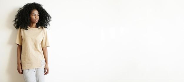 Красота и мода. изолированный снимок красивой стильной женщины с афро-стрижкой в большой футболке и хлопковых штанах в помещении