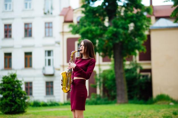 Красота и мода, музыка. красивая женщина с саксофоном.