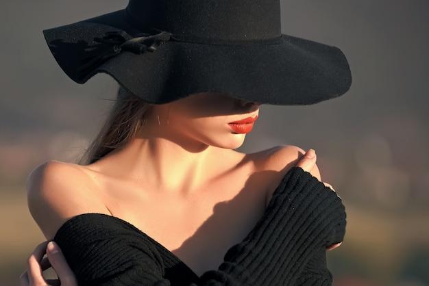 아름다움과 패션. 검은 모자에 예쁜 젊은 여자.