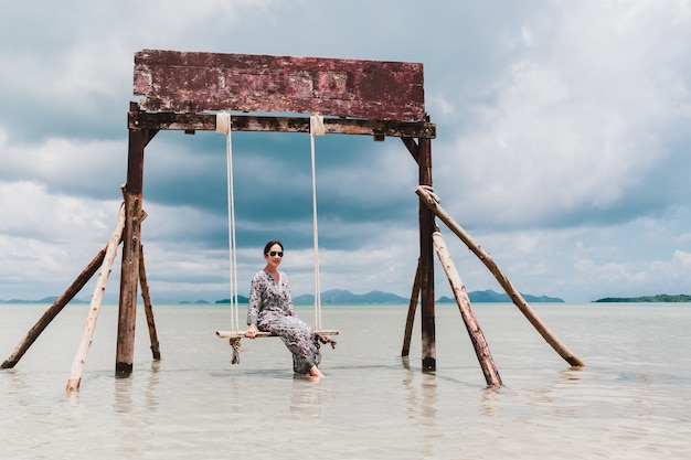 Женщина красоты и моды ослабляя на стуле качелей в море.