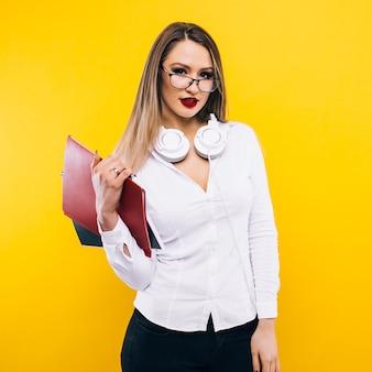 美容とファッション。長いブロンドの髪を持つ女教師。セクシーなファッショナブルなドレスとメガネの女子学生。黄色の壁にファッションモデルのポーズ。見た目とファッションスタイル