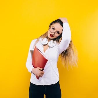 아름다움과 패션. 긴 금발 머리를 가진 여자 선생님. 섹시 한 유행 드레스와 안경에 여자 학생입니다. 노란색 벽에 패션 모델 포즈입니다. 외모와 패션 스타일