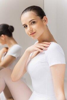 美しさと優雅さ。彼女の肩に触れ、鏡の近くに座ってカメラを見ている美しい若いバレリーナ