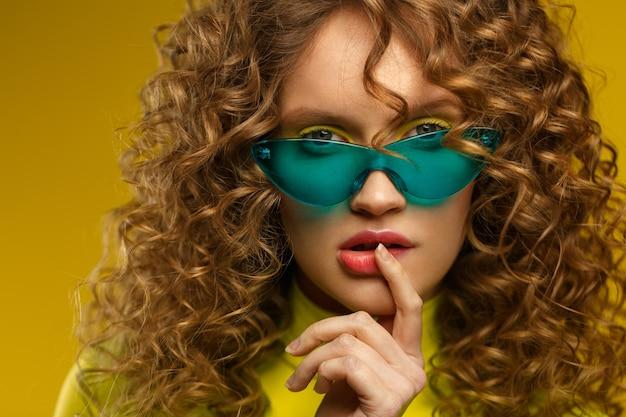 美容とヘアケアのコンセプト。巻き毛の若い美しい女性のファッションスタジオの肖像画。