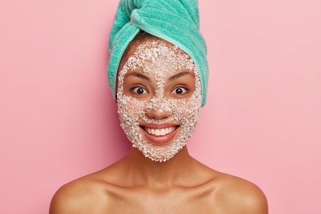 美容とヘルスケアのコンセプト。満足している暗い肌の女性のクローズアップ画像は、白いスクラブフェイシャルマスクを適用し、彼女の顔色の純度と柔らかさを気にし、頭にターコイズブルーのタオルを持っています