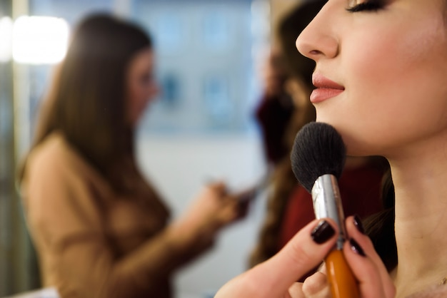 若い女性モデルの美と健康のきれいな肌。ブラシでパウダーファンデーションを適用する女性