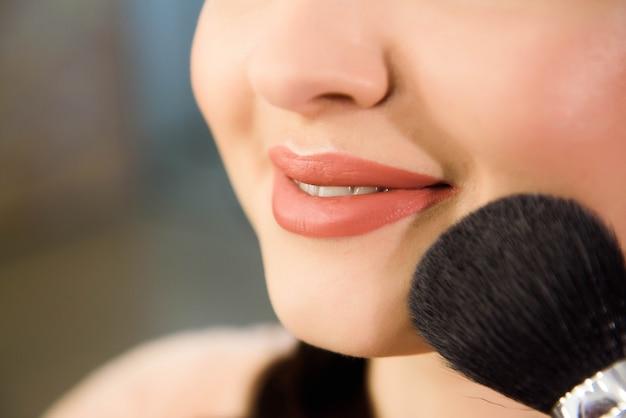 젊은 여성 모델의 아름다움과 건강 깨끗한 피부. 브러쉬로 파우더 파운데이션을 적용하는 여자.