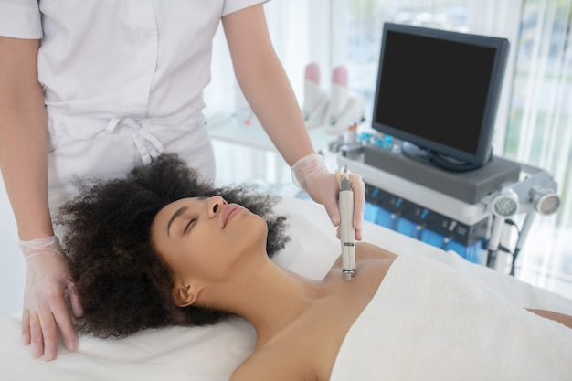 美しさと健康。美容センターでの手順中に横たわっている若い女性とハードウェア手順を実行する美容師の手