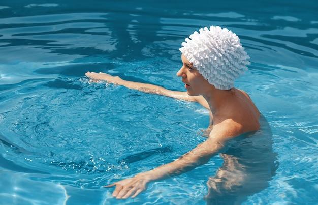 아름다움과 건강한 라이프 스타일 개념입니다. 수영장에서 아름 다운 젊은 누드 여자. 젊은 벌거 벗은 여자는 수영장에서 수영을 즐긴다