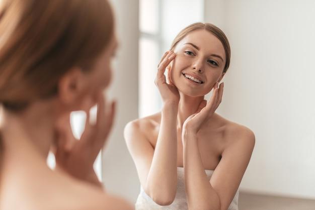 Красавица и ее отражение в зеркале. вид через плечо на привлекательную женщину, касающуюся ее лица и улыбающуюся, проводя время дома