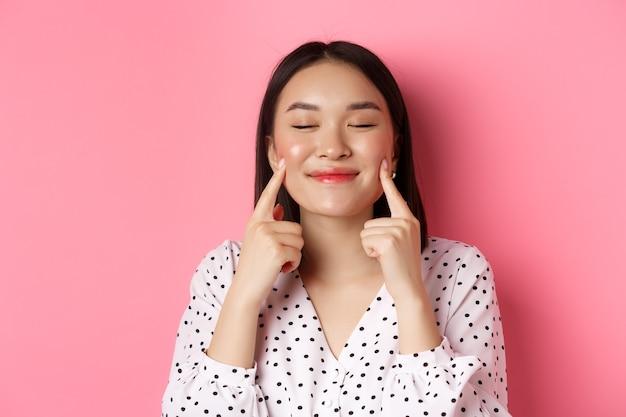 美容とライフスタイルのコンセプト。目を閉じて頬を突っつい、満足して笑って、ピンクの背景の上に立っている美しいアジアの女性のクローズアップ。