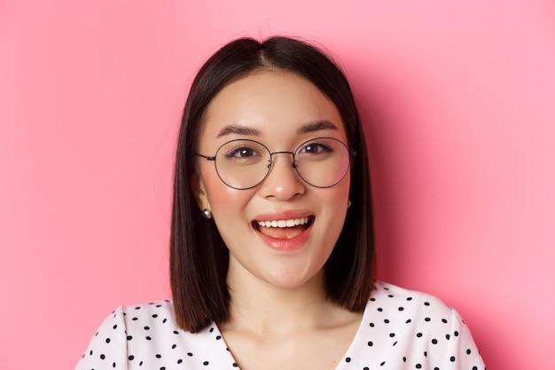 美容とライフスタイルのコンセプト。トレンディなメガネをかけて、カメラで幸せそうに笑って、ピンクの背景に立っているかわいいアジアの女性モデルのクローズアップ。