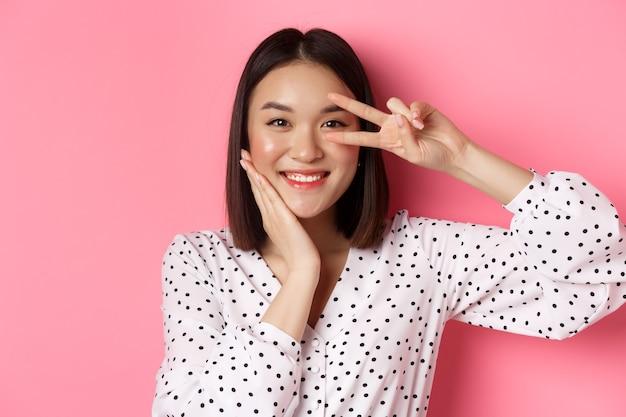 美容とライフスタイルのコンセプト。平和の兆候を示し、頬に触れ、カメラに幸せな笑みを浮かべて、ピンクの背景の上に立っているかわいいアジアの女性のクローズアップ