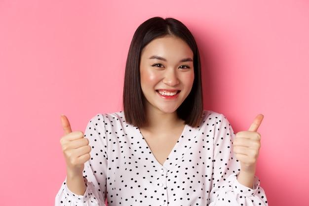 美容とライフスタイルのコンセプト。ピンクの背景の上に立って、サポートを示し、親指を立てるジェスチャーをし、あなたのように、そしてあなたを称賛する笑顔を作るかわいいアジアの女性のクローズアップ