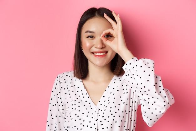 아름다움과 라이프 스타일 개념. 드레스에 분홍색 배경 위에 서 눈에 괜찮아 기호를 보여주는 귀여운 미소 아시아 여자의 근접