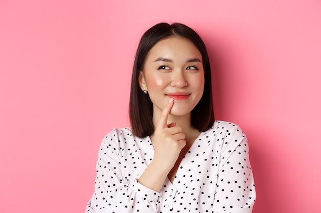 Концепция красоты и образа жизни. крупный план мечтательной азиатской девушки, улыбающейся, смотрящей влево и думающей, делающей выбор, стоящей на розовом фоне