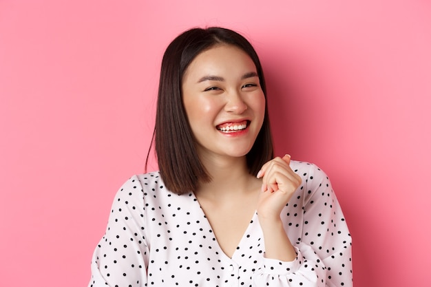 아름다움과 라이프 스타일 개념입니다. 핑크색 배경 위에 서서 웃고, 행복해 보이고, 진정한 감정을 보여주는 행복한 아시아 여성의 클로즈업.
