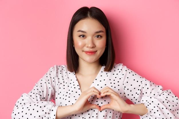 美容とライフスタイルのコンセプト。ピンクの背景の上に立って、ハートのサインを示し、バレンタインデーに笑顔とロマンチックな気分の素敵なアジアの女性のクローズアップ。