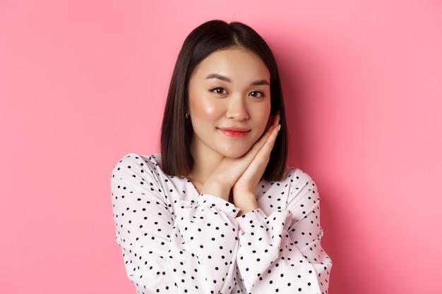 美容とライフスタイルのコンセプト。手のひらに寄りかかって、憧れのカメラを見て、ピンクの背景の上に立っているかわいい韓国の女の子のクローズアップ。