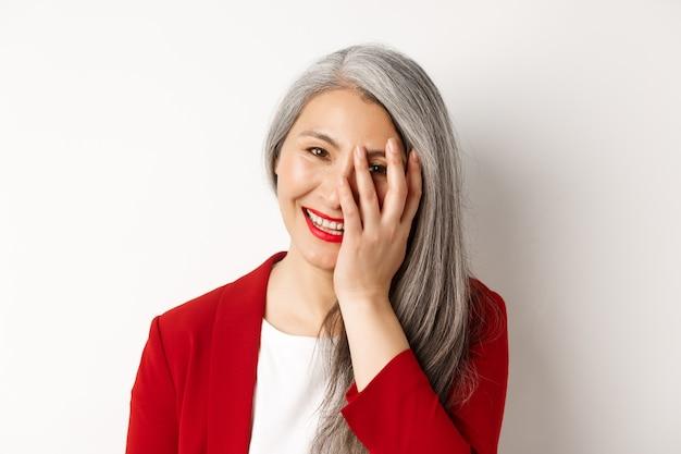 아름다움과 메이크업 개념. 아름 다운 아시아 성숙한 여자, 웃으면 서 얼굴을 만지고, 행복 하 게 웃 고, 흰색 배경 위에 서 닫습니다.