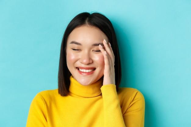 Концепция красоты и макияжа. закройте красивой азиатской женщины, смеющейся и выглядящей покрасневшей от комплиментов, стоя на синем фоне.
