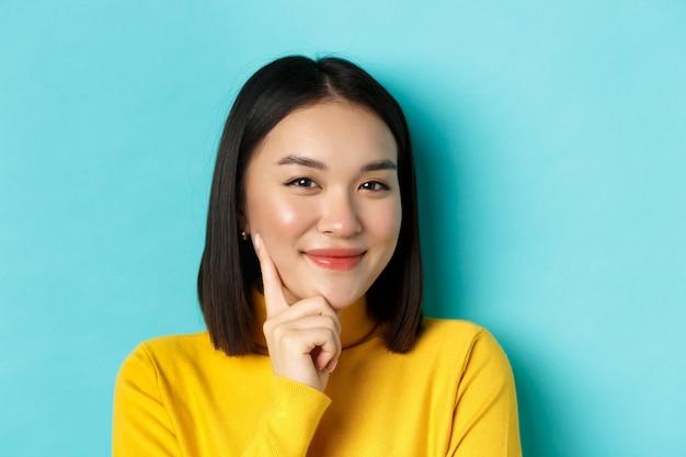 아름다움과 메이크업 개념. 파란색 배경 위에 서있는 생각을 갖는 카메라와 미소에 만족 찾고 사려 깊은 아시아 여자의 닫습니다.