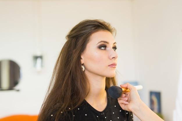 美容とメイクのコンセプト-ブラシでプロのメイクをしている美しい女性のクローズアップの肖像画。