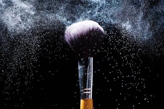 Концепция красоты и макияжа. косметика кисти, выпуская облако розового сверкающего пудры на черном фоне.